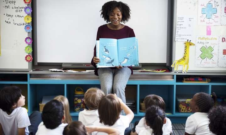 a teacher with a book working with their students